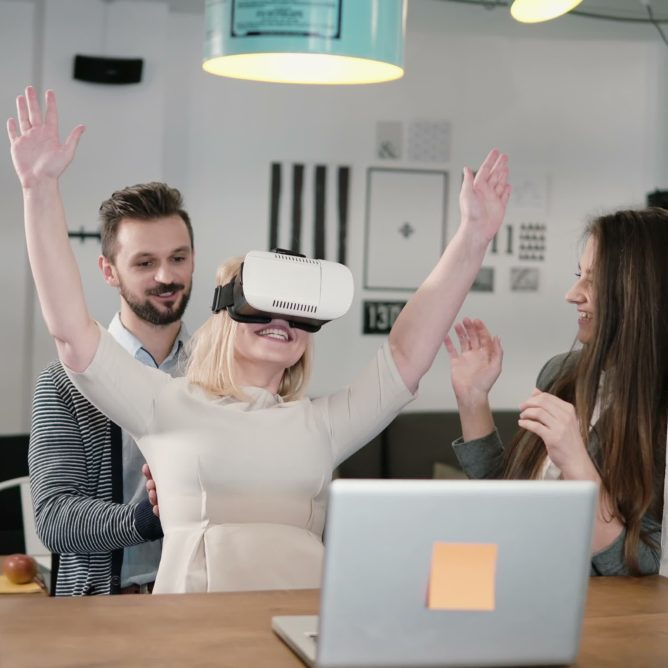 first experience with virtual reality glasses young team supports young beautiful blond girl in modern startup office